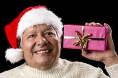 Upphetsad gamal man med Santa Cap And Magenta Gift Royaltyfri Foto