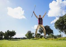 Upphetsad golfare som hoppar upp innehavklubban Arkivfoto