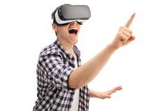 Upphetsad grabb som använder en VR-hörlurar med mikrofon arkivfoton