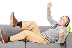 Upphetsad hög man som placeras på en lyssnande musik för modern soffa Royaltyfria Foton