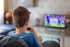 Upphetsad hållande ögonen på fotbollsmatch för liten unge i TV Royaltyfri Bild