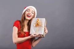 Upphetsad julkvinna som bär den Santa Hat Enjoying Of A gåvan arkivfoto