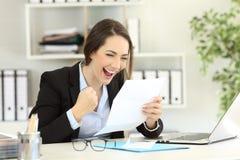 Upphetsad kontorsarbetare som läser ett brev fotografering för bildbyråer