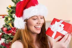 Upphetsad kvinna i ask för gåva för santa hatt hållande Fotografering för Bildbyråer
