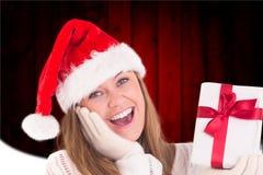 Upphetsad kvinna i den santa hatten som rymmer en julgåva under jultid Fotografering för Bildbyråer