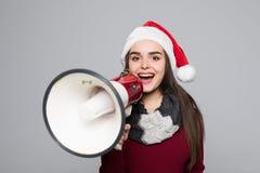 Upphetsad kvinna i hållande megafon för santa hatt över grå bakgrund Fotografering för Bildbyråer