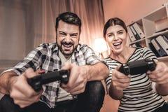 Upphetsad kvinna och man som spelar en videospel Royaltyfria Bilder