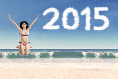 Upphetsad kvinna på stranden med nummer 2015 Arkivbilder