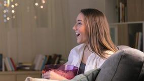 Upphetsad kvinna som äter hållande ögonen på tv för popcorn arkivfilmer