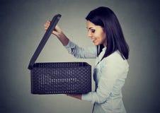 Upphetsad kvinna som öppnar en ask med en överraskning royaltyfri foto