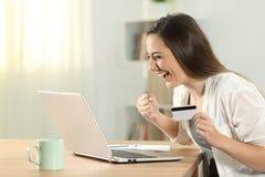 Upphetsad kvinna som direktanslutet hemma betalar royaltyfri bild