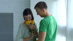 Upphetsad kvinna som förvånas av gruppen av blommor från man