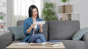Upphetsad kvinna som hemma läser en kupong arkivfilmer