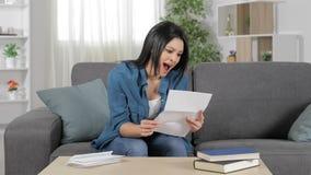 Upphetsad kvinna som hemma läser ett brev arkivfilmer