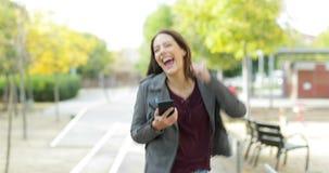 Upphetsad kvinna som kontrollerar telefonen som firar goda nyheter