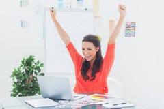 Upphetsad kvinna som lyfter henne armar, medan arbeta på hennes bärbar dator Arkivbild