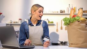 Upphetsad kvinna som ser den pappers- påsen med grönsaker som är lyckliga med matleverans arkivfoton