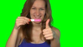Upphetsad kvinnavisninggraviditetstest med två band och blick på kameran arkivfilmer