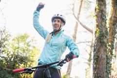Upphetsad kvinnlig bergcyklist i skog Royaltyfri Bild