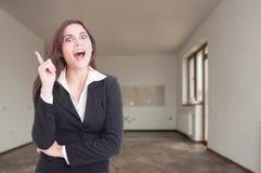 Upphetsad kvinnlig fastighetsmäklare som har en stor idé Arkivfoto