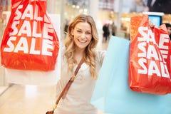 Upphetsad kvinnlig shoppare med Sale påsar i galleria Arkivfoto