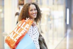 Upphetsad kvinnlig shoppare med Sale påsar i galleria Royaltyfri Fotografi