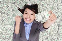 Upphetsad ligga för affärskvinna på pengarsäng royaltyfri bild
