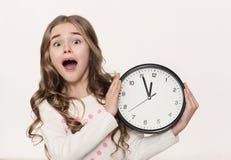 Upphetsad liten flicka med klockan på vit bakgrund arkivbild