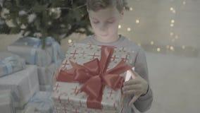 Upphetsad liten lycklig ask för gåva för gåva för jul för pojkebarnöppning i dekorerat rum för atmosfär för träd för nytt år fest lager videofilmer