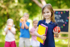 Upphetsad liten skolflicka som tillbaka går till skolan Royaltyfria Bilder