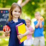 Upphetsad liten skolflicka som tillbaka går till skolan Royaltyfri Bild