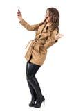 Upphetsad lycklig kvinna som bär det beigea laget som tar selfie med mobiltelefonen Arkivfoto