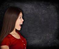 Upphetsad lycklig kvinna vid svart tavla/den svart tavlan Arkivfoto