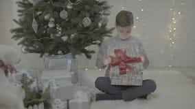 Upphetsad lycklig liten ask för gåva för gåva för jul för pojkebarnöppning i dekorerat rum för atmosfär för träd för nytt år fest lager videofilmer