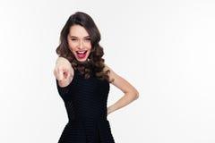 Upphetsad lycklig säker lockig retro utformad kvinna som pekar på kameran royaltyfri foto