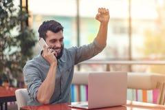 Upphetsad lycklig skäggig freelancer som läser emailen med resultat om seger i den moderna online-striden som sitter på bärbara d arkivfoton
