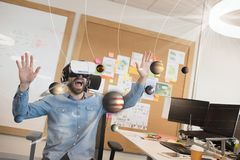 Upphetsad man i VR-hörlurar med mikrofon som ser planeter 3D Arkivfoto