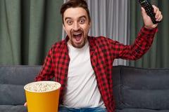 Upphetsad man med hållande ögonen på fotboll för popcorn royaltyfria bilder