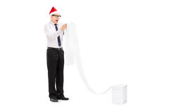 Upphetsad man med jultomtenhatten som läser en lång lista Fotografering för Bildbyråer