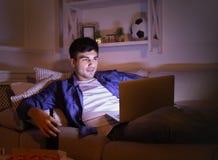Upphetsad man som äter pizza och håller ögonen på film på bärbara datorn arkivfoto