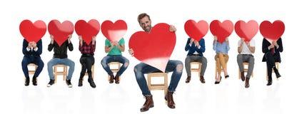 Upphetsad man som framme visar hjärta av en grupp arkivbild