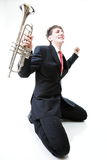 Upphetsad man som knäfaller med trumpeten, i hand och att skrika. Isolat Royaltyfri Foto
