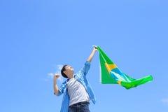 Upphetsad man som rymmer den Brasilien flaggan Royaltyfri Fotografi