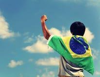 Upphetsad man som rymmer en Brasilien flagga Royaltyfria Bilder