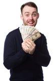 Upphetsad man som rymmer en handfull av pengar Arkivbild