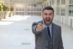 Upphetsad man som skrattar och pekar på kameran royaltyfri foto