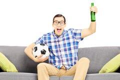 Upphetsad manlig sportfan med fotbollbollen och den hållande ögonen på sporten för öl Arkivfoton