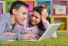Upphetsad moder och son med den moderna b?rbara datorn arkivfoto