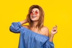 Upphetsad moderiktig kvinna som skrattar på apelsinen royaltyfri bild