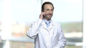 Upphetsad mogen doktor som talar på mobiltelefonen stock video